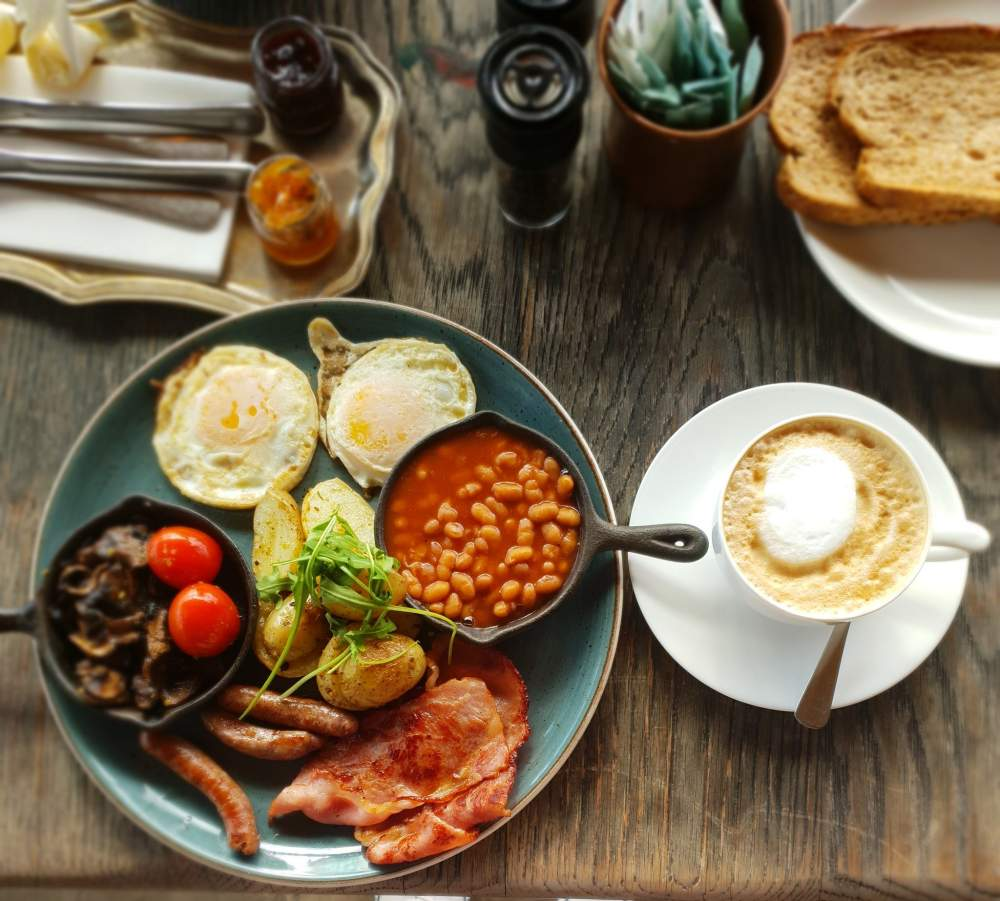 Brown bread sunny side up sussages bacon potatoes baked beans mushrooms cappuccino SA